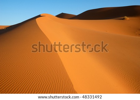Two people on top of a distant dune - stock photo