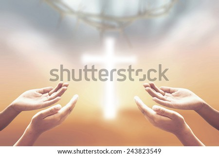 Two people open empty hands with palms up, over blurred crown of thorns and the white cross on beautiful sunset background. - stock photo