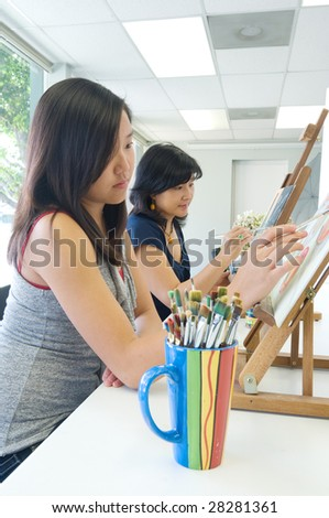 Two people painting in a classroom situation - stock photo