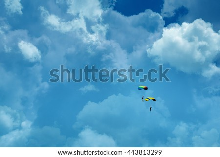 two people parachuting in cloudy sky - stock photo