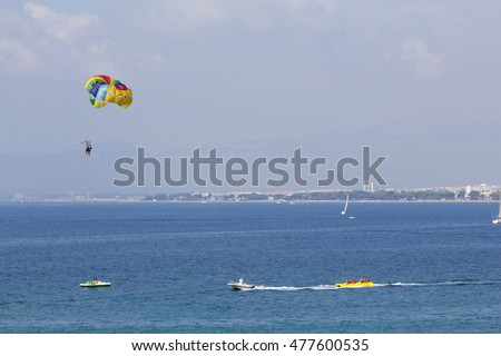 Two people parasailing in the sea at summer, assisted by a boat