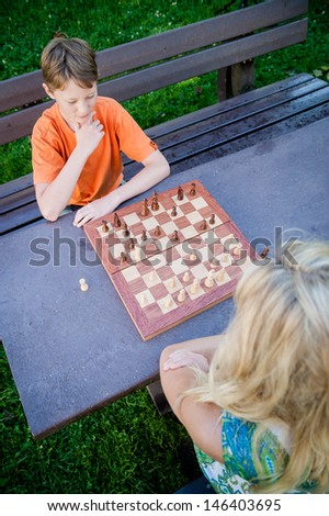 Two people playing chess in the park - stock photo