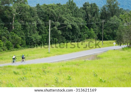 Two people ride  bicycle in the way on the hill