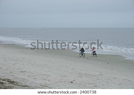 Two people riding bicycles alone on a winter beach - stock photo