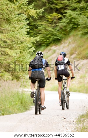 Two people riding their mountain bikes