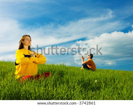 Two people sitting in an open field of green grass on a bright sunny day; meditating. - stock photo