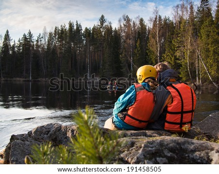 Two people sitting on the bank of the river on a background of trees - stock photo