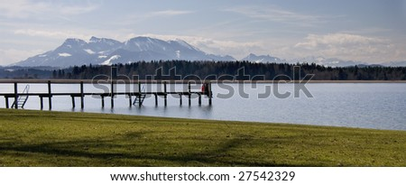 Two people sitting on the landing at the Chiemsee with the alps in the background