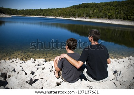Two people sitting on the rocky shore of a lake. - stock photo