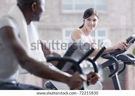 Two people speaking together while biking at health club, foucs on the girl - stock photo
