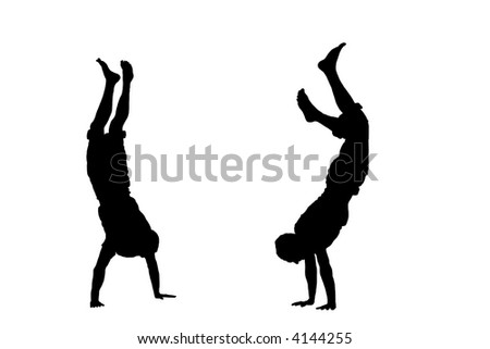 Two people standing on their hands - silhouette - stock photo
