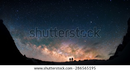 Two people standing together holding hands against the Milky Way galaxy in the mountains. Nepal, Himalayas, Everest region, Gokyo (4,790 m). - stock photo