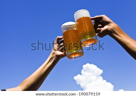 Two people toasting with two glasses of beer outside. - stock photo