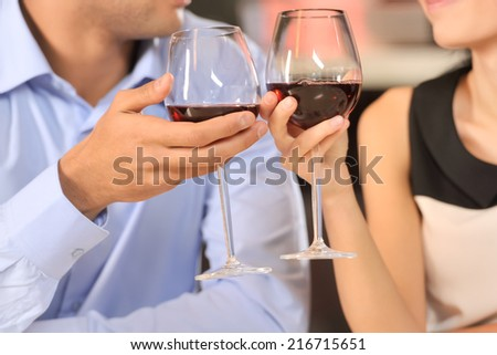 Two people toasting with wine glasses. cropped image of couple drinking red wine at restaurant - stock photo