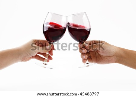 Two people toasting with wine glasses filled with red wine - stock photo