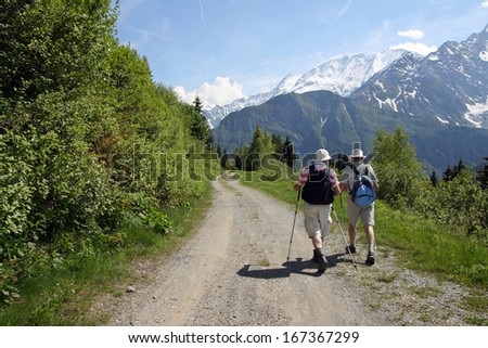 Two people walk on ground road in mountains - stock photo