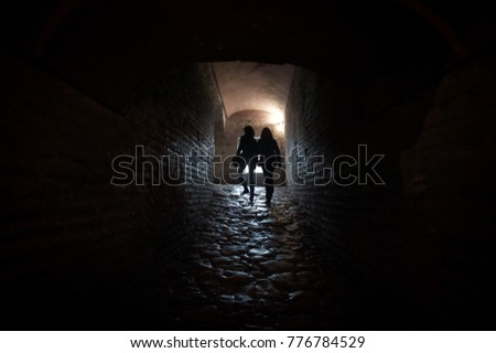 Two people walking in a passage way of an old building