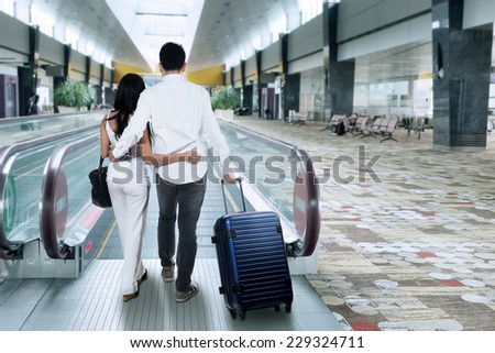 Two people walking on escalator while carrying a luggage in the airport hall - stock photo