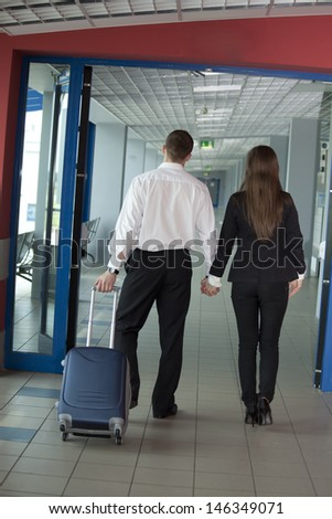 Two people walking with suitcase - stock photo