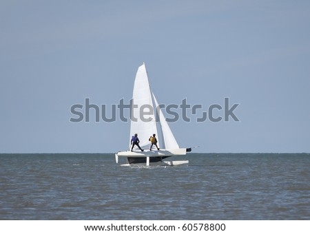 Two people wearing trapeze harnesses on a catamaran at full speed
