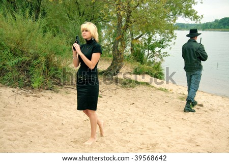Two people with guns, on the river beach, duel - stock photo