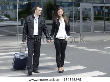 Two people with suitcase at the airport parking - stock photo