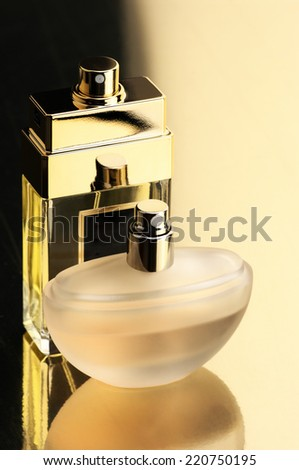 Two perfume bottles on gold background with reflection. - stock photo