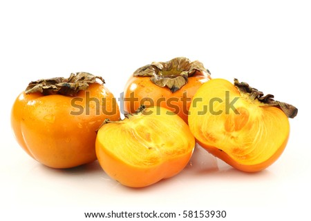 two persimmon fruit and two halves on a white background
