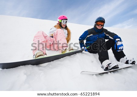 Two person sit on snow and preparing to ride from the hill - stock photo