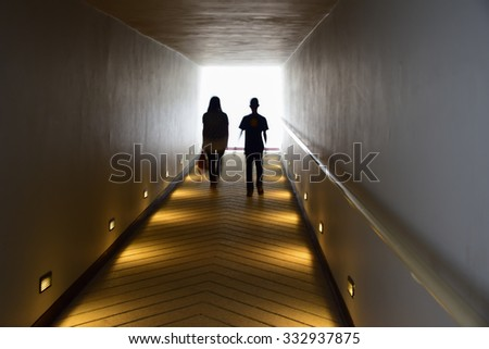 Two person stand at  end of the tunnel. - stock photo