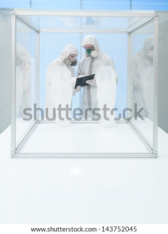 two persons in protective suits and breathing masks looking over some data from a clipboard, next to an empty sterile chamber - stock photo