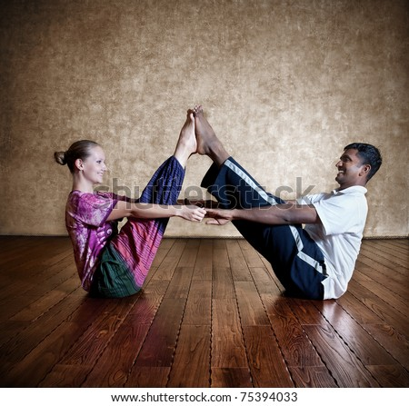 Two persons: Indian man and Caucasian woman in bright purple Indian cloth doing couple yoga nauka asana boat pose at the grunge background with wooden floor - stock photo