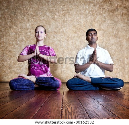 Two persons: Indian man and Caucasian woman in bright purple Indian cloth doing yoga padmasana lotus posture at the grunge background with wooden floor - stock photo