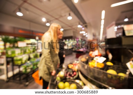 Two persons shopping for fruit in a supermarket, Out of focus shot for use as a background or backdrop - stock photo
