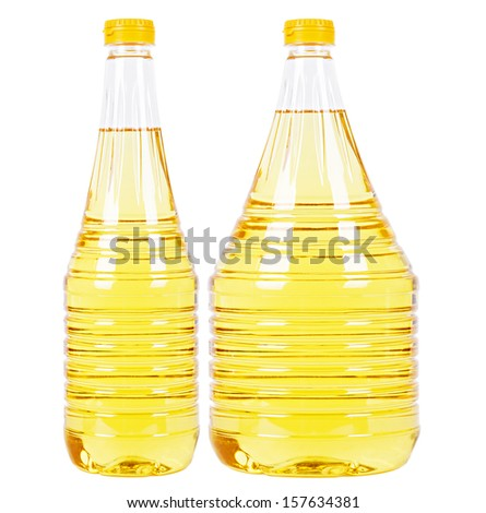 Two pet bottles (thin one and thick one) filled with yellow vegetable oil and yellow caps isolated on white - stock photo