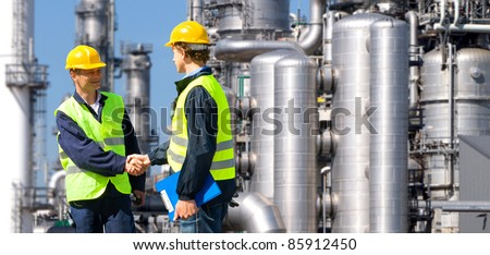 Two petrochemical contractors closing a deal in front of an oil refinary - stock photo