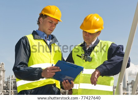 Two petrochemical engineers wearing safety vests and a hard top going over a checklist - stock photo