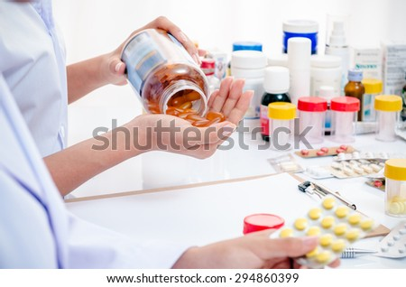 two pharmacists holding medicine capsule and tablet  - stock photo