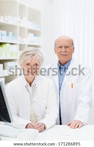 Two pharmacists standing behind the counter in the pharmacy in their white lab coats smiling at the camera in front of stocked shelves - stock photo