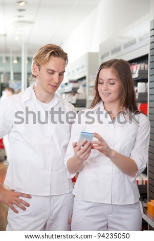 Two Pharmacists With Pharmaceuticals In Hand Consulting Each Other In A Pharmacy. - stock photo