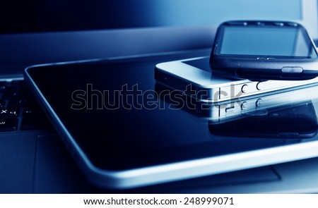 two phones and tablet pc on laptop - stock photo