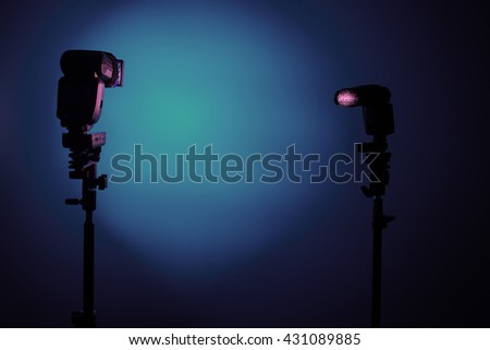 Two Photo camera flash speedlights with honeycombs on stands strobes. Blue background - stock photo