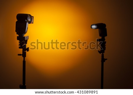 Two Photo camera flash speedlights with honeycombs on stands strobes. Home studio lighting kit. Orange background - stock photo