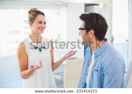 Two photo editors speaking together in office - stock photo