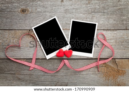 Two photo frames over wooden background with red ribbon and candy hearts - stock photo