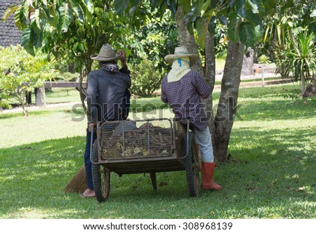 Two picking up garbage man take a rest  by sitting on tray fill with dry leave