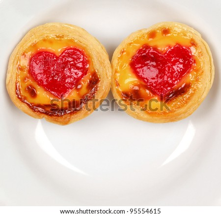 Two pie cake with strawberry heart shape at the center on white dish - stock photo