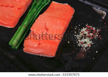 two piece of fresh raw pink salmon on black tray with rosemary and asparagus dry spices healthy food diet cooking concept - stock photo