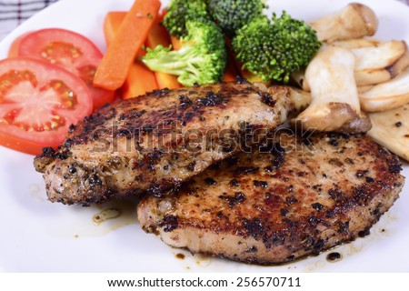 Two piece of pork steak and appetizer - stock photo
