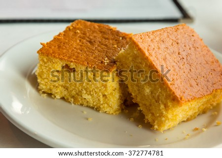 Two pieces of cornbread on a white plate - stock photo